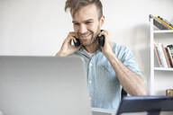 Smiling man with headphones and laptop at desk in office - VPIF01781