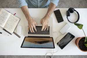 Top view of man using laptop at desk in office - VPIF01784