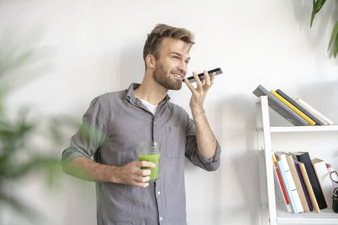 Smiling man using smartphone in office - VPIF01787
