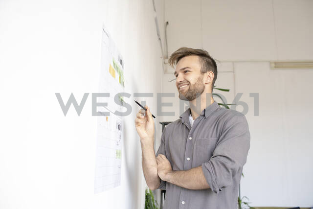 Smiling man working on paper at the wall in office - VPIF01796 - Vasily Pindyurin/Westend61