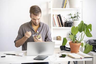 Man having lunch break at desk in office - VPIF01799