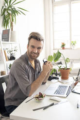 Portrait of smiling man with smartphone having lunch break at desk in office - VPIF01802