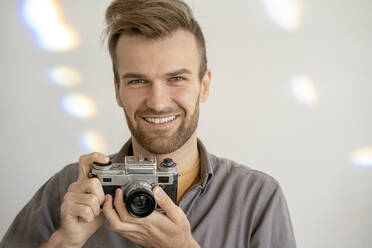 Portrait of smiling man holding old-fashioned camera - VPIF01814