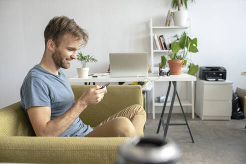 Smiling man sitting on couch in office using smartphone - VPIF01817