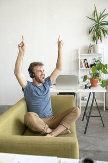 Excited man sitting on couch in office listening to music - VPIF01820