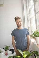 Portrait of smiling man standing at the window in office - VPIF01823
