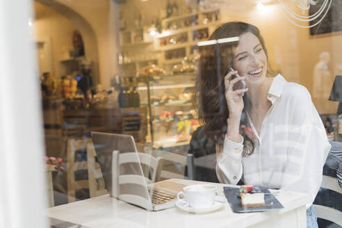 Happy woman on the phone in a cafe - FMOF00761