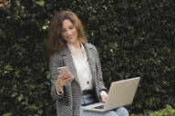 Smiling woman using smartphone and laptop outdoors - FMOF00770