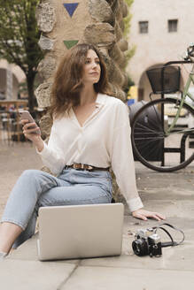 Young woman with smartphone, camera and laptop outdoors - FMOF00788