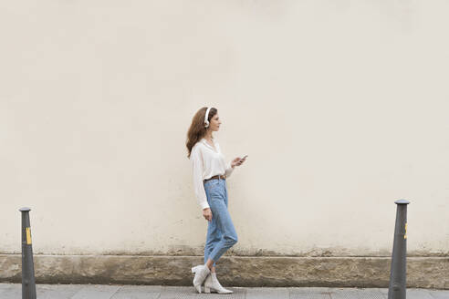 Young woman with smartphone and headphones on sidewalk - FMOF00797