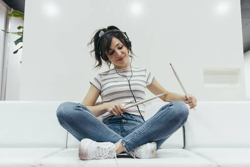 Smiling woman listening to music and playing with drum sticks - MTBF00223