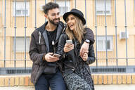 Portrait of laughing young couple with  their mobile phones in the city - ERRF02167