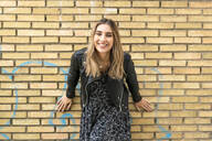 Portrait of laughing young woman in front of brick wall - ERRF02173
