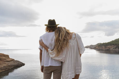 Back view of young couple in love standing in front of the sea, Ibiza, Balearic Islands, Spain - AFVF04255