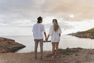 Back view of young couple in love standing in front of the sea, Ibiza, Balearic Islands, Spain - AFVF04267