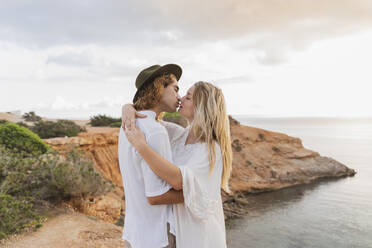 Kissing young couple in love in front of the sea, Ibiza, Balearic Islands, Spain - AFVF04270