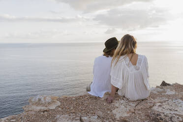 Back view of young couple sitting on rock in front of the sea, Ibiza, Balearic Islands, Spain - AFVF04273