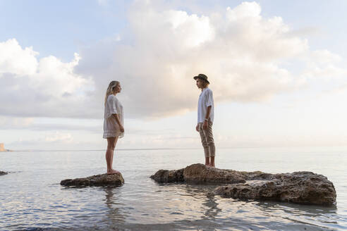 Young couple standing on rocks in front of the sea, Ibiza, Balearic Islands, Spain - AFVF04276