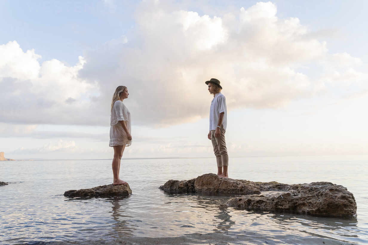 Young couple standing on rocks in front of the sea, Ibiza, Balearic Islands, Spain - AFVF04276 - VITTA GALLERY/Westend61