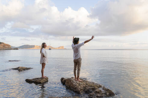 Young couple standing on rocks in front of the sea, Ibiza, Balearic Islands, Spain - AFVF04279