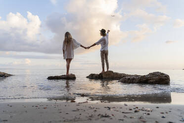 Back view of young couple standing on rocks in front of the sea, Ibiza, Balearic Islands, Spain - AFVF04282