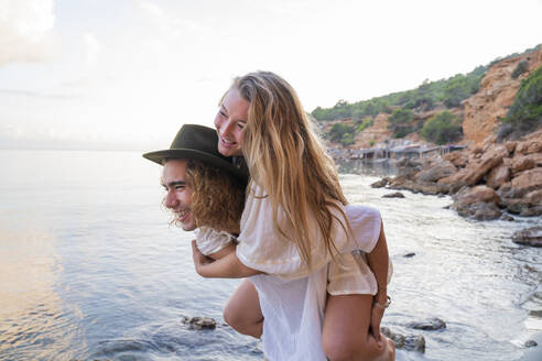 Young man giving his girlfriend a piggyback ride in front of the sea, Ibiza, Balearic Islands, Spain - AFVF04285