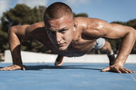 Portrait of barechested muscular man doing pushups outdoors - RCPF00135