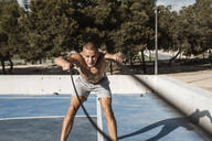 Barechested muscular man exercising with battle ropes outdoors - RCPF00141