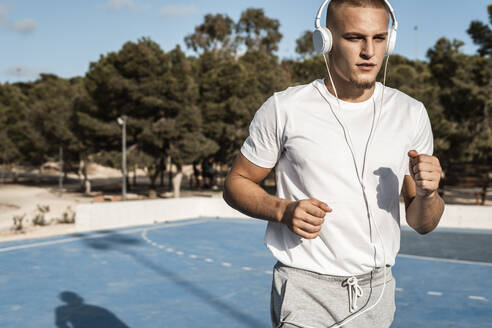 Young man with headphones running outdoors - RCPF00147