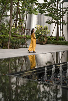 Fashionable woman dressed in yellow strolling in the city - MAUF03124