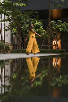Fashionable woman dressed in yellow dancing in the city - MAUF03127
