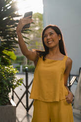Portrait of fashionable woman dressed in yellow taking selfie with smartphone - MAUF03133