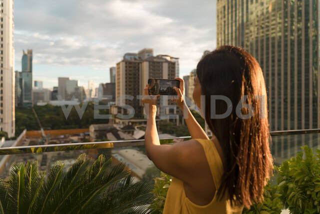 Back view of woman standing on roof terrace taking photo with smartphone, Bangkok, Thailand - MAUF03136 - Mauro Grigollo/Westend61