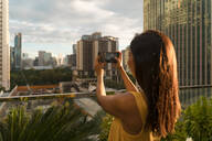Back view of woman standing on roof terrace taking photo with smartphone, Bangkok, Thailand - MAUF03136