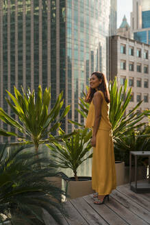 Smiling woman standing on roof terrace looking at distance, Bangkok, Thailand - MAUF03139