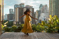 Back view of woman dancing on roof terrace, Bangkok, Thailand - MAUF03142