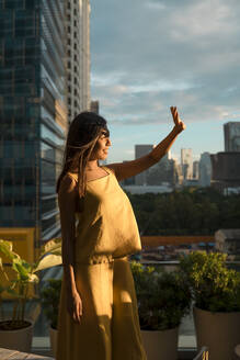 Woman standing on roof terrace watching sunset, Bangkok, Thailand - MAUF03145