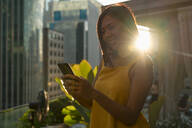 Portrait of happy woman on roof terrace at backlight looking at cell phone - MAUF03148