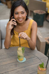 Portrait of smiling woman on the phone sitting in a cafe with a drink - MAUF03151