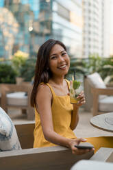 Portrait of happy woman sitting in a cafe with a drink - MAUF03154