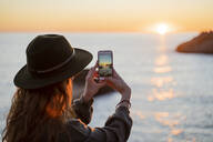 Young woman using smartphone on beach during sunset, Ibiza - AFVF04291