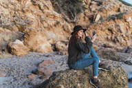 Young woman using smartphone on beach during sunset, Ibiza - AFVF04294