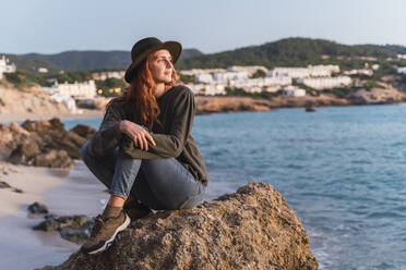 Young woman sitting on the beach and enjoying sunset, Ibiza - AFVF04297