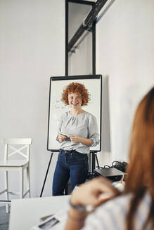 Smiling businesswoman leading a presentation at flip chart in conference room - ZEDF02711