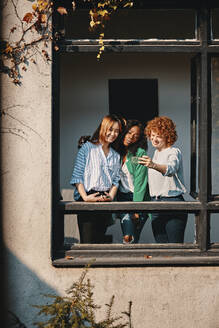 Three businesswomen standing at the window of an office building taking a selfie - ZEDF02771