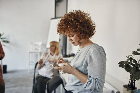 Businesswoman having a break in office using smartphone - ZEDF02780