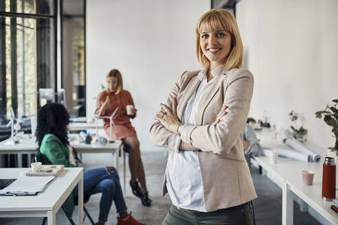 Portrait of confident pregnant businesswoman in office with colleagues in background - ZEDF02783