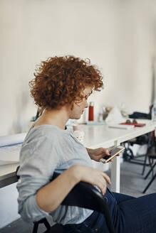 Businesswoman having a break in office using smartphone - ZEDF02789