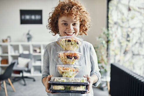 Portrait of smiling businesswoman holding stack of takeaway food in office - ZEDF02792