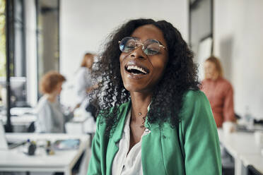 Portrait of a laughing businesswoman in office with colleagues in background - ZEDF02810